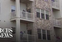 Residents of Wisconsin senior living facility sing from balconies